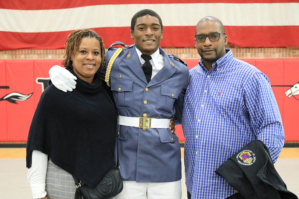Cadet with arms around his parents